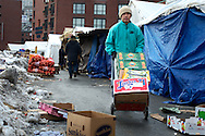 February 12, 2011 - A man walks behind the vendor tents at Haymarket, pushing a hand truck loaded with produce. Photo by Lathan Goumas.