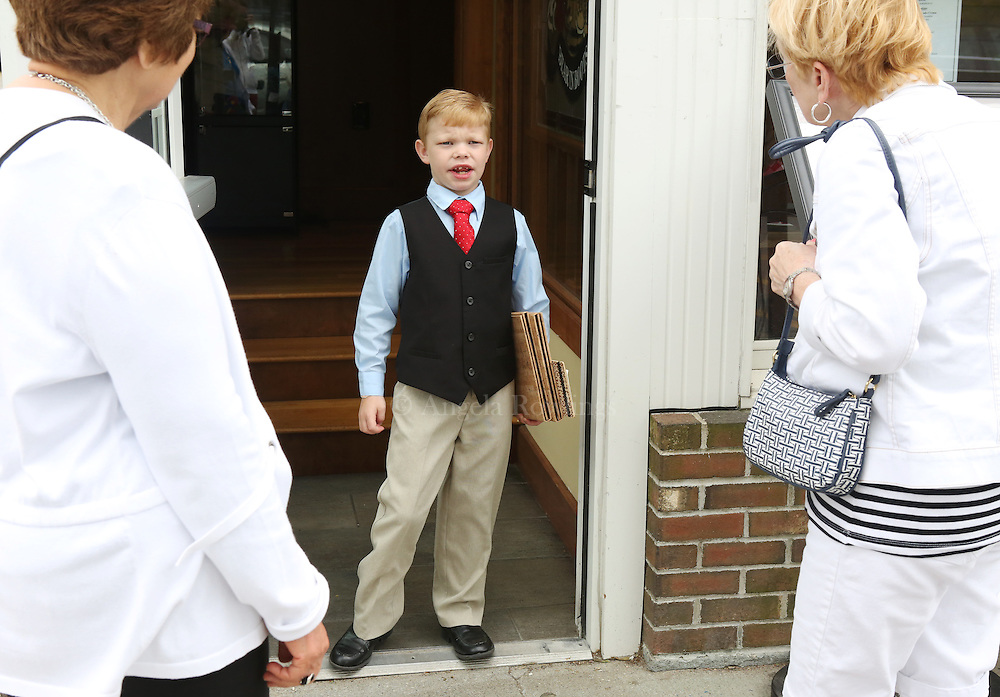 (Falmouth, MA - 5/28/15) Charlie Rickard, 8, who works weekends as a maitre d' in his parents' Falmouth restaurant, Bear in Boots, talks with women outside the restaurant, Thursday, May 28, 2015. He says he is better on the computer than his mom, so he is able to update the tables quickly, and he enjoys talking with people. Staff photo by Angela Rowlings.