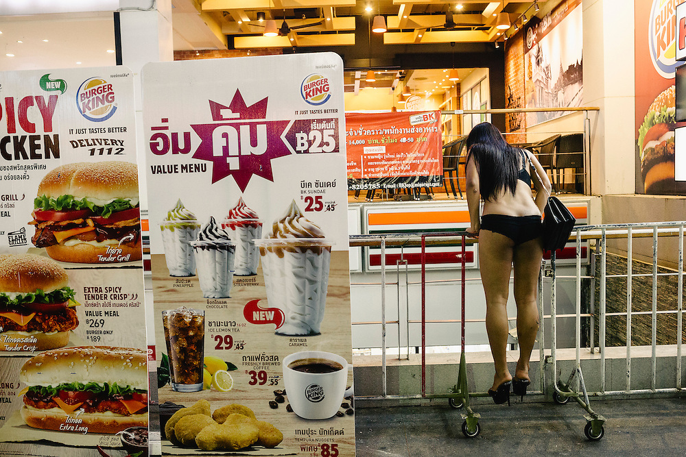 A working girl looks over the banisters at her friend on Bangla Street. The infamous street is where all the GoGo bars and discotheques are located on the island.