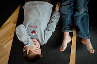 JEROME A. POLLOS/Press..Miles Kison, 5, tries to concentrate on relaxing as he lays alongside his classmate Charles McCoy, also 5, during a yoga class Monday. Children from Kinder Magic in Coeur d'Alene learned various poses and relaxation methods as part of the field trip to Parkside Fitness.