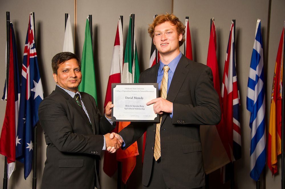 Coalgate native David Mowdy (right), an agricultural economics major, receives an Oklahoma State University Alvin and Susietta Berg Scholarship from OSU associate professor Gopal Kakani (left) at the university's recent College of Agricultural Sciences and Natural Resources Scholarships and Awards Banquet. The scholarship is part of more than $1.4 million in scholarships and awards presented to CASNR students for the 2016-2017 academic year. (Photo by Todd Johnson)