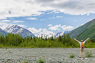 A hiker rejoices in the scenic view as he looks toward Eagle Glacier in the Icicle Creek Wilderness region of Chugach State Park in Southcentral Alaska. Spring. Afternoon.