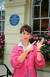 Woman signing in front of Virginia Woolf blue plaque, UK