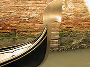 The prow of a gondola gliding through a canal, Venice, Italy