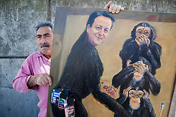 © Licensed to London News Pictures. 19/07/2013. London, England. Artist Kaya Mar poses with one of his oil paintings of Prime Minister David Camera painting the three monkeys and with cigarette packages stuck to it. It was painted by Mar in protest of David Cameron denying any involvement with the tobacco lobby. Photo credit: Bettina Strenske/LNP