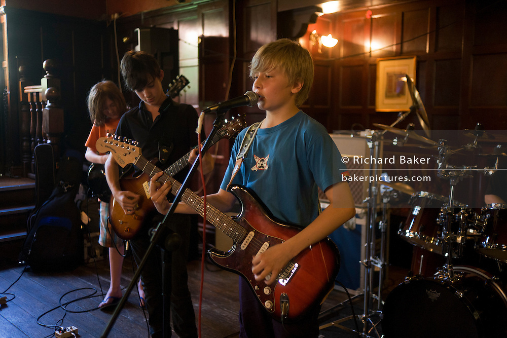 Schoolboys perform rock and roll song together as a band in a south London pub.