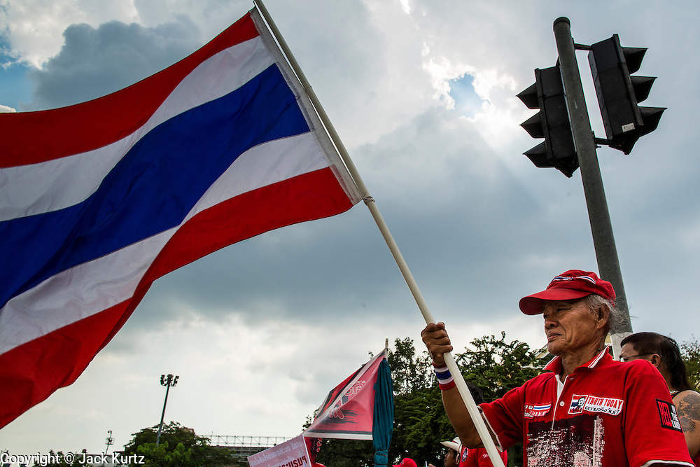 "10 DECEMBER 2012 - BANGKOK, THAILAND:  A Red Shirt protestor waves the Thai flag during a protest for constitutional reform on Ratchadamnoen Avenue in Bangkok Monday. The Thai government announced on Monday, which is Constitution Day in Thailand, that will speed up its campaign to write a new charter. December 10 marks passage of the first permanent constitution in 1932 and Thailand's transition from an absolute monarchy to a constitutional monarchy. Several thousand ""Red Shirts,"" supporters of ousted and exiled Prime Minister Thaksin Shinawatra, motorcaded through the city, stopping at government offices and the offices of the Pheu Thai ruling party to present demands for a new charter.        PHOTO BY JACK KURTZ"