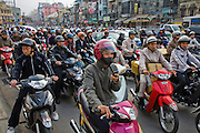 Motorcyclists approach a busy traffic intersection on a street in Hanoi, Vietnam. Motorcycles are the most common mode of transport in Vietnam.