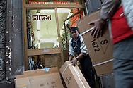 """Roma (Italy), 26/03/2004: Lavoratori asiatici trasportano scatole nel negozio di occhiali, ombrelli e bigiotteria """"Shodesh Coop""""..© Andrea Sabbadini"""