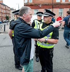 Pictured: A protester argues with police officers.<br /> <br /> Protesters gathered outside the main Home Office building in Glasgow to protest at private company SERCO's attempts to evict failed asylum seekers from their homes.<br /> <br /> &copy; Dave Johnston / EEm