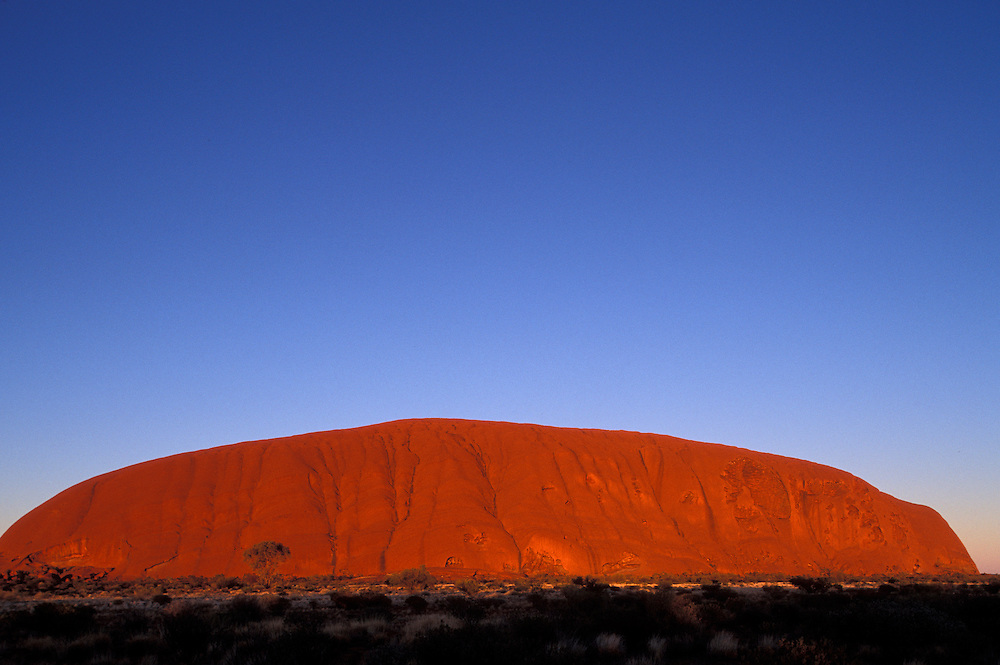 Australia, Northern Territory, Light from the rising sun turns Ayers Rock bright red in desert at Uluru National Park