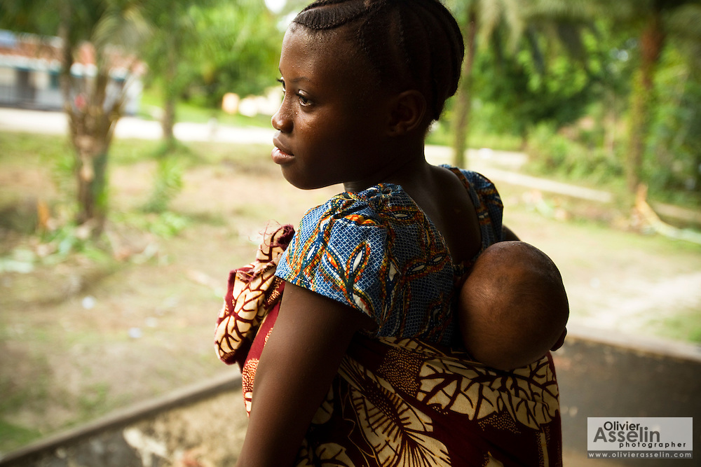 Elizabeth Farma, 16, carries her two-month-old son Emmanuel on her back near the Bonthe district hospital in Bonthe, Sierra Leone on Wednesday April 21, 2010. Elizabeth still attends high school, and leave the child with her grandmother while she is in class.