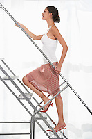 Young woman wearing high heeled shoes walking up aluminium staircase side view