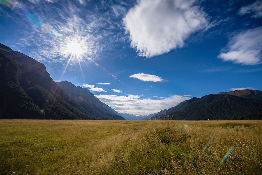 Mountain range and empty field with blue sky and sun flare surrounding Fiordland National Park