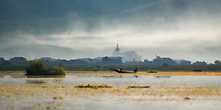 A fisherman tends to his lines on Inlé Lake, Burma (Myanmar), with a Buddhist monastery in the background.