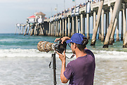 Photographer on the beach at the US open Surfing at Huntington Beach, California, July 27 2016