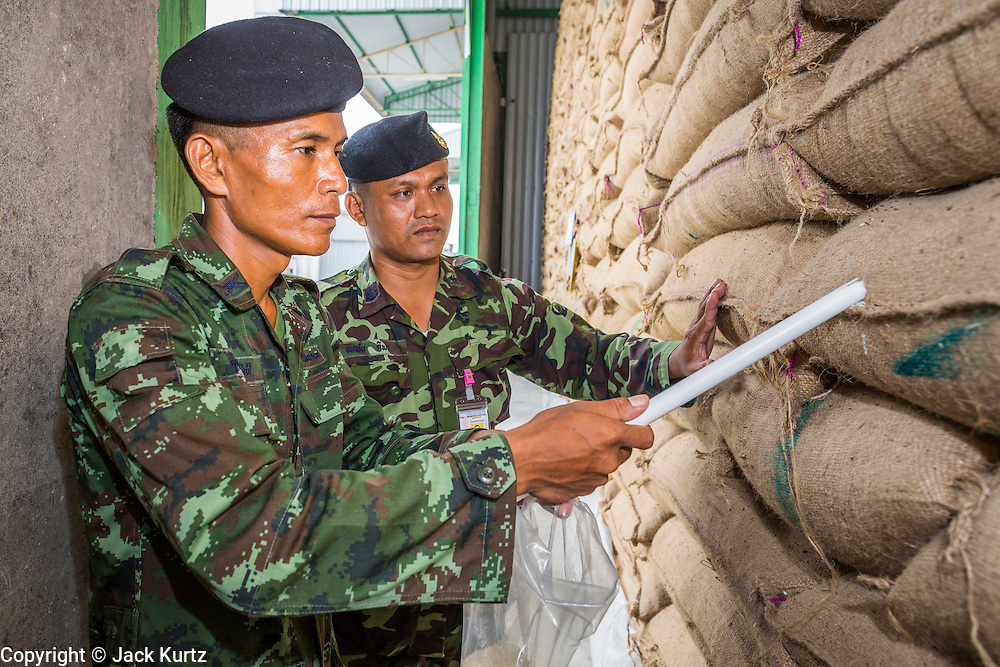 "08 JULY 2014 - WANG NAM SAP, SUPHAN BURI, THAILAND: Thai soldiers draw samples of rice from burlap bags at a rice warehouse in Wang Nam Sap, Suphan Buri province. Representatives of the Thai ruling junta have started inspecting stocks of rice bought by the ousted civilian government following the 2012 and 2013 rice harvests. The government of ousted former Prime Minister Yingluck Shinawatra bought up thousands of tons of rice from farmers at above market prices in one of its most controversial populist policies. The alleged mismanagement of the ""rice pledging scheme,"" as it was called, was one of the factors that lead to the May 2014 coup that ousted the government. According to officials doing the inspections found rotten and weevil-infested grain, along with evidence that large stocks were replaced with old or inferior grades.     PHOTO BY JACK KURTZ"