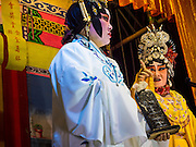 "18 AUGUST 2014 - BANGKOK, THAILAND:   Members of the Lehigh Leng Kaitoung Opera troupe perform at Chaomae Thapthim Shrine, a small Chinese shrine in a working class neighborhood of Bangkok. The performance was for Ghost Month. Chinese opera was once very popular in Thailand, where it is called ""Ngiew."" It is usually performed in the Teochew language. Millions of Chinese emigrated to Thailand (then Siam) in the 18th and 19th centuries and brought their culture with them. Recently the popularity of ngiew has faded as people turn to performances of opera on DVD or movies. There are still as many 30 Chinese opera troupes left in Bangkok and its environs. They are especially busy during Chinese New Year and Chinese holiday when they travel from Chinese temple to Chinese temple performing on stages they put up in streets near the temple, sometimes sleeping on hammocks they sling under their stage. Most of the Chinese operas from Bangkok travel to Malaysia for Ghost Month, leaving just a few to perform in Bangkok.      PHOTO BY JACK KURTZ"