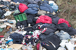 © Licensed to London News Pictures. 29/03/2018. London, UK. A large pile of waste and rubbish, and here some bags of cloths, have been dumped in an area of scrap land next to houses and a recreation park in Edmonton, north London. Local residents are calling it a 'river of rubbish' and say it has been there for a month and are campaigning for it's removal.  Photo credit: Peter Macdiarmid/LNP