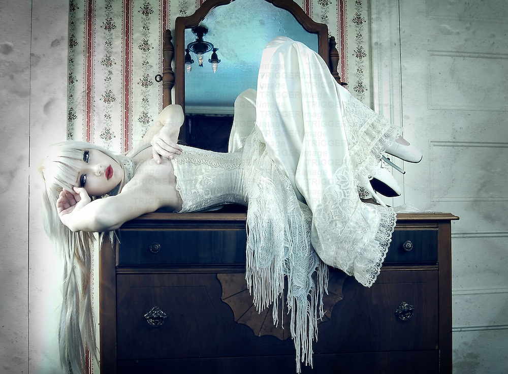 A young woman with long blonde hair wearing a white corset lying on a dressing table