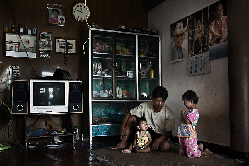 PHANG NGA PROVINCE,SOUTHERN THAILAND,AUGUST 2012: A Moken fisherman and his two children in their house in Chaipattana tsunami village. After the tsunami some Moken families were granted an accommodation.<br /> The Moken are a nomadic sea people who live in and around southern Thailand, traditionally feeding of the fruits of the sea for eight months a year. But the 2004 Indian Ocean tsunami destroyed many livelihoods, and the Moken were forced onto the land.<br /> Brought to the world's attention by the natural disaster, the seafaring tribe is struggling to reconcile tradition and modernity, leaving behind their &quot;sea gypsy&quot; life for a modern existence