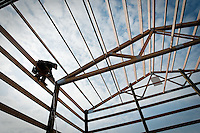 JEROME A. POLLOS/Press..Isaiah Yandt, with Steel Structures America, finishes framing work Monday on a shop building at a home in Hayden. Steel Structures America is one of about 50 vendors who will take part in Thursday's At Home in North Idaho Expo at The Coeur d'Alene Resort.