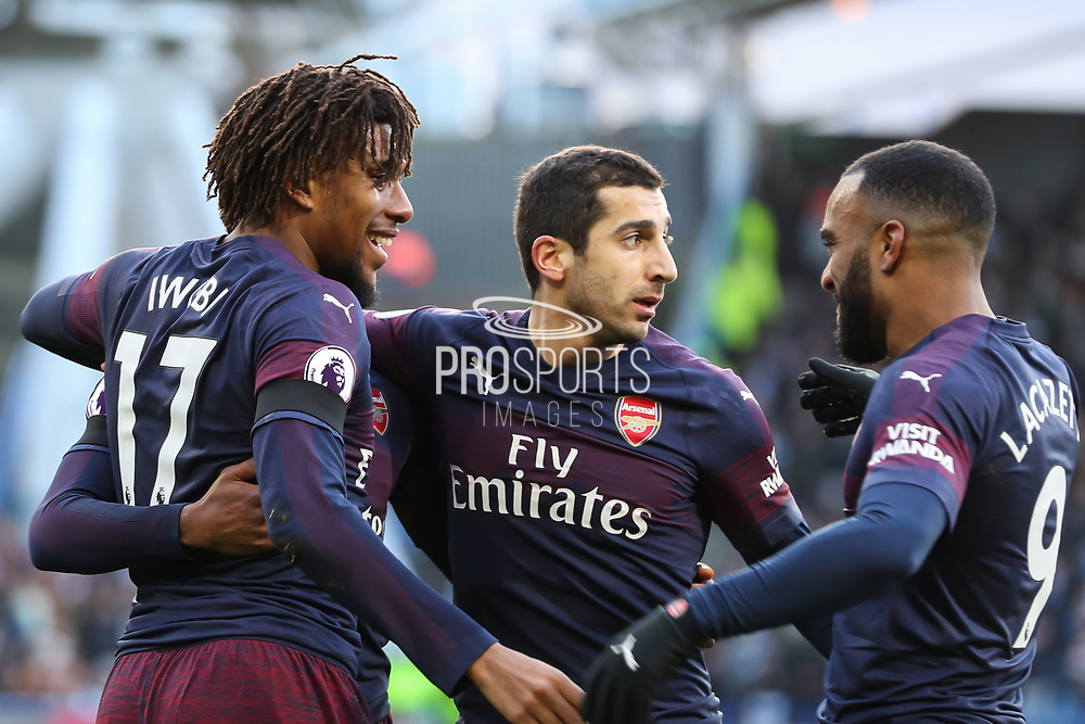 Arsenal forward Alex Iwobi (17) celebrates with this team mates Arsenal midfielder Henrikh Mkhitaryan (7) and Arsenal forward Alexandre Lacazette (9) after scoring his team's first goal during the Premier League match between Huddersfield Town and Arsenal at the John Smiths Stadium, Huddersfield, England on 9 February 2019.