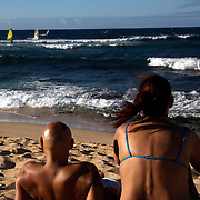 Sunbathers watch windsurfers at Hookipa Beach in Maui during September of 2008.  The north shore of Maui is one of the best windsurfing spots in the world, and annually holds championship in both surfing and windsurfing.