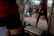 """Ilya (left in mirror) train with punching bags in Rompo Muay Thai Gym, Khlong Toei, Bangkok city, Thailand on 14th December 2009..Ilya Bashes, aged 27, from Herzeliya, Israel, has been fighting seriously for 5 years. He met Shuki in a muay thai seminar in Israel and decided immediately that he would come to Thailand to train under Shuki. """"I knew he was serious from the look in his eyes,"""" says Shuki. Ilya has since been to Thailand 3 times, for 6 months each time. Ilya is rapidly gaining a good reputation in Thailand as a strong fighter. When back in Israel, he works as a Sushi chef in an expensive restaurant. Ilya 's family is of Russian heritage, very non-religious. """"Chabad keeps the people together yet it doesn't push religion on to people."""".Photo by Suzanne Lee / For Chabad Lubavitch"""