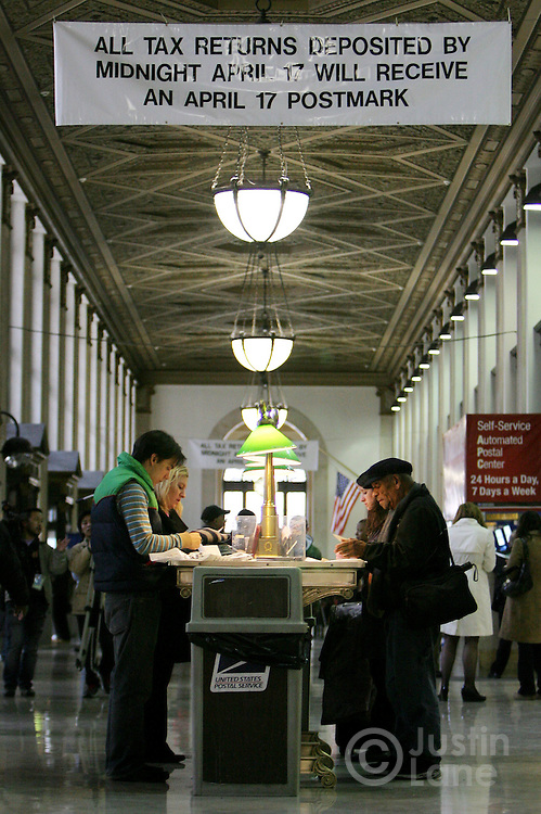 A group of people work on mailing their income tax returns at a post office in New York, New York on 17 April 2007.  US citizens are required to have their tax returns mailed by midnight on 17 April 2007.