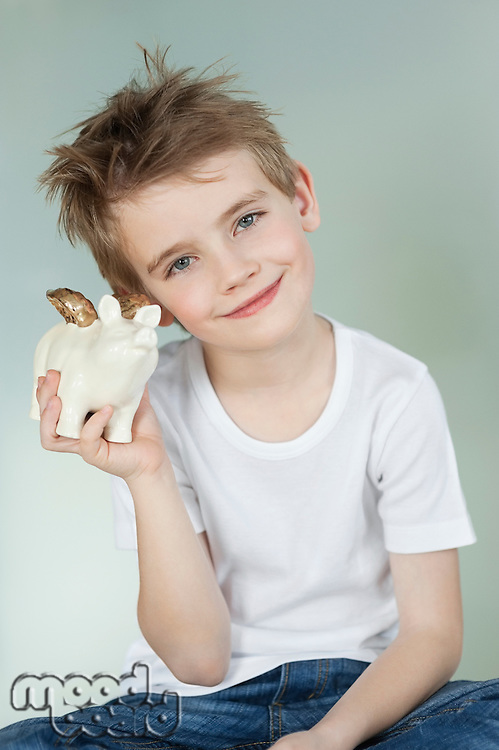 Boy holding a piggy bank over gray background