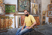 Artist in His Studio With Finished Paintings