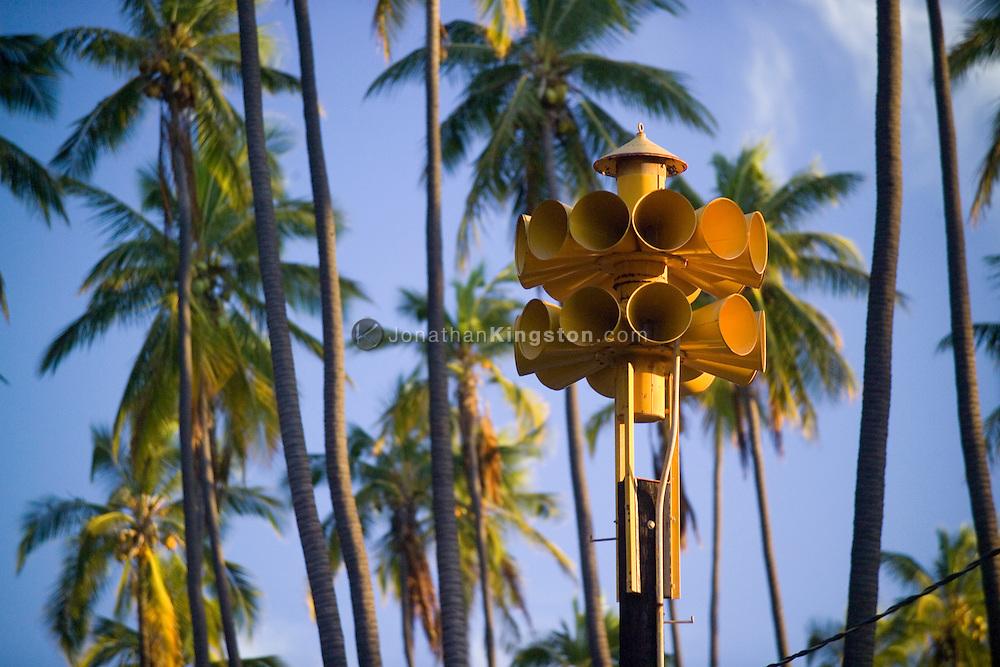 MOLOKAI, HI - Tsunami warning system sirens and palm trees on the Pacific island of Molokai, Hawaii.