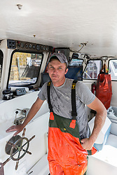 "Captain Matt Clemmons in the wheelhouse of ""Mean Kathleen"" at Potts Harbor Lobster in Harpswell, Maine."