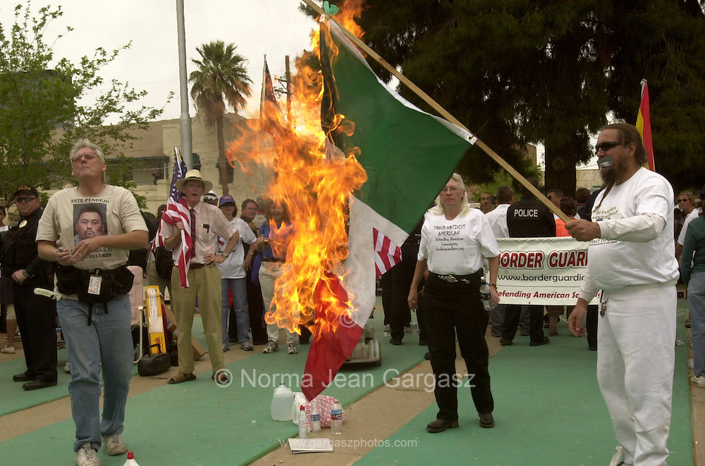 Counter protestors, Roy Warden, (left), Laine Lawless, and Russ Dove, burn the flag of Mexico at Armory Park, which served as the destination for thousands who marched in protest of propsed immigration legislation, on April 10, 2006, In Tucson, Arizona, USA.