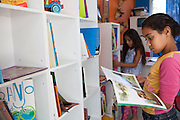 Giovana choosing a book to read from one of the bookshelves in the community library, Biblioteca Comunitaria do Arquipelago, Porte Alegre, Brazil. <br /> <br /> Cirandar is working in partnership with  C&A and C&A Instituto to implement a network of Community Libraries in eight communities of Porto Alegre.