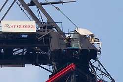 © Licensed to London News Pictures. 17/01/2013. London, UK. Workmen are seen examining the top of a crane attached to the St George's Wharf development hit by a helicopter in Vauxhall, London, yesterday (17/01/13). 2 (two) people, including the pilot, died as a result of the incident and a further 11 (eleven) injured after the Augusta 109 helicopter collided with the crane in heavy mist showering wreckage onto cars below. Photo credit: Matt Cetti-Roberts/LNP