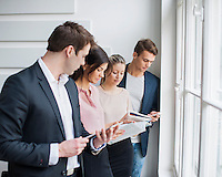 Young business people working by window in office