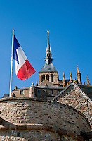 The towers of Mont St. Michel with the French flag flying against a blue sky,