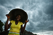 A teenage girl uses a plastic bin to protect herself from the rain in Porto Novo, Benin on Sunday October 24, 2010.