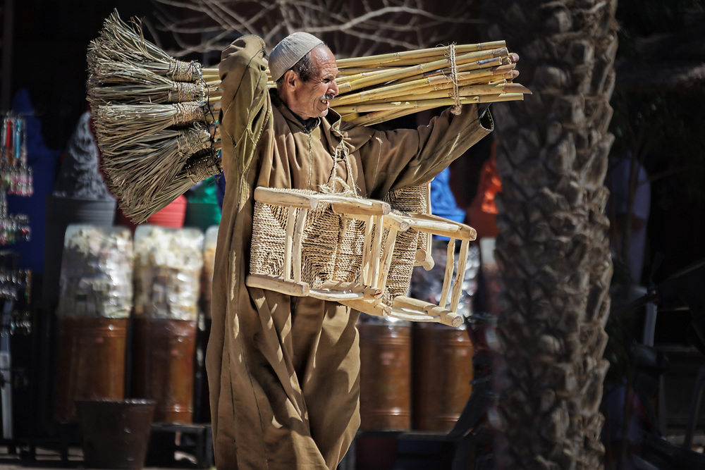 A street seller carries handmade chairs and brooms. Street scene in the medina of Marrakech, Morocco.