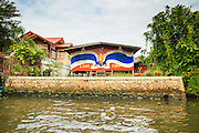 "17 NOVEMBER 2012 - BANGKOK, THAILAND:  Traditional housing along a canal in the Thonburi section of Bangkok, painted with a Thai flag and homage to Bhumibol Adulyadej, the King of Thailand. Bangkok used to be known as the ""Venice of the East"" because of the number of waterways the criss crossed the city. Now most of the waterways have been filled in but boats and ships still play an important role in daily life in Bangkok. Thousands of people commute to work daily on the Chao Phraya Express Boats and fast boats that ply Khlong Saen Saeb or use boats to get around on the canals on the Thonburi side of the river. Boats are used to haul commodities through the city to deep water ports for export.    PHOTO BY JACK KURTZ"