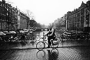 Een man fietst in de regen over de grachten in Amsterdam.<br />