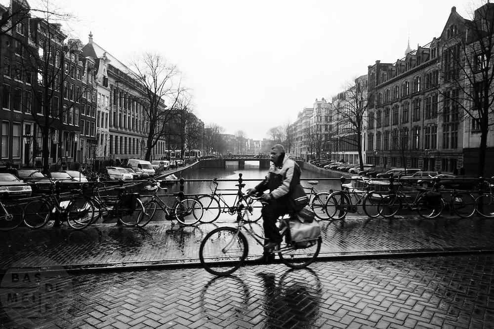 Een man fietst in de regen over de grachten in Amsterdam.<br /> <br /> A man is cycling in the rain over the canals in Amsterdam.