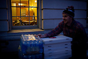 A legislator works late as James McBride of Ian's Pizza pushes a load of pizzas donated to protestors at the State Capitol in Madison, WI, February 23, 2011.