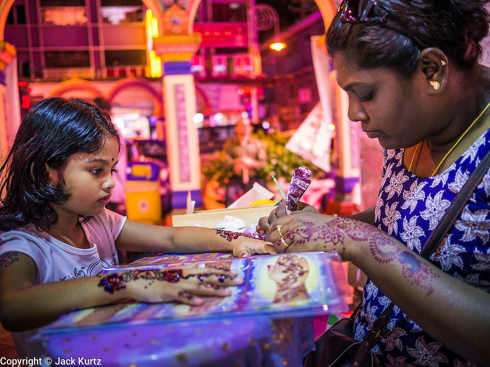 "20 DECEMBER 2012 - KUALA LUMPUR, MALAYSIA: A girl gets a henna tattoo from a henna tattoo seller on Jalan Tun Sambanthan, the main street in ""Brickfields,"" the Little India section of Kuala Lumpur, Malaysia. The ""Little India"" section of Kuala Lumpur is also known as ""Brickfields."" The area has recently been renovated and has emerged as a tourist draw. It's within walking distance of KL Stesen Sentral, the Kuala Lumpur central train station.    PHOTO BY JACK KURTZ"