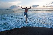 A boy jumps into the ocean.
