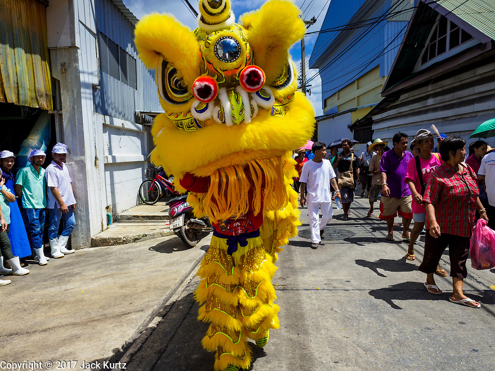 "02 JUNE 2017 - SAMUT SAKHON, THAILAND: Lion dancers perform during the parade for the City Pillar Shrine in Samut Sakhon. The Chaopho Lak Mueang Procession (City Pillar Shrine Procession) is a religious festival that takes place in June in front of city hall in Samut Sakhon. The ""Chaopho Lak Mueang"" is  placed on a fishing boat and taken across the Tha Chin River from Talat Maha Chai to Tha Chalom in the area of Wat Suwannaram and then paraded through the community before returning to the temple in Samut Sakhon. Samut Sakhon is always known by its historic name of Mahachai.      PHOTO BY JACK KURTZ"