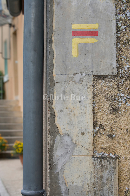 close up of markings on the corner of a house indicating the direction on a rambling path France