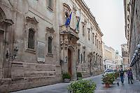 Palazzo Carafa. Palazzo Carafa insieme alla sua chiesetta adiacente, fu costruito dal vescovo Sozi-Carafa, da cui ne ereditò il nome, intorno alla metà del Cinquecento per sostituire il precedente edificio mal messo. Nel tempo è stato abitato da diversi ordini monastici fino a quando il vescovo Nicola Caputo lodestituì dalla sua originaria funzione di sede religiosa per passarlo nelle mani della Provincia di Lecce che lo proclamò sua sede definitiva.<br /> <br /> In seguito a questo passaggio di consegne la struttura fu modificata sia internamente che esternamente per essere adattata alle nuove esigenze funzionali del Palazzo, aprendo sulle strade di Lecce ariose finestre e eleganti balconi in stile Neoclassico. Ancora oggi Palazzo Carafa è uno dei poli amministrativi di Lecce, in quanto è la sede del Comune.